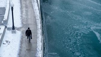 CHICAGO, IL - DECEMBER 27: A pedestrian walks along the Chicago River on December 27, 2017 in Chicago, Illinois. Frigid temperatures will be dipping into the single digits in the Midwest over the next few days as Chicago faces one of the coldest holidays in a decade.  (Photo by Kamil Krzaczynski/Getty Images)