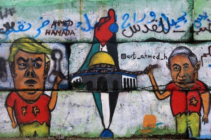 A mural in Gaza depicts U.S. President Donald Trump with Israeli President Benjamin Netanyahu in Israel. Trump appeared to threaten U.S. aid to the Palestinians in a series of tweets Tuesday.