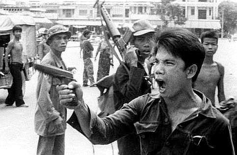 A Khmer Rouge soldier waves his pistol and orders store owners to abandon their shops in Phnom Penh, Cambodia on April 17, 19