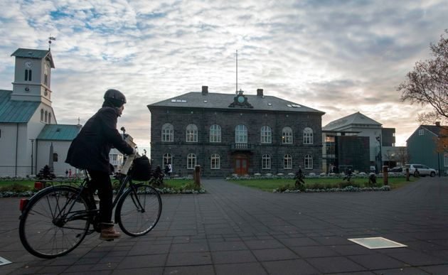 A woman cycles past the Althingi Parliament building in Reykjavik,