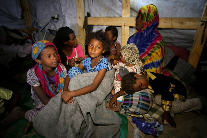 Members of a family displaced by war in the northwestern areas of Yemen sit in their makeshift hut on a street in the Red Sea