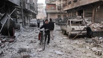 A Syrian boy pushes a bicycle down a street amidst the destruction following reported shelling by Syrian government forces, in the rebel-held town of Douma in Syria's eastern Ghouta region, on November 17, 2017. Shelling by the Syrian regime on the rebel-held Eastern Ghouta, which has been besieged since 2013 and where humanitarian conditions are dire, killed at least 10 civilians, among them six children, the Syrian Observatory for Human Rights said. The deaths were the result of the latest bout in an escalating cycle of tit-for-tat attacks between regime forces and the rebels holding the enclave on the Syrian capital's eastern outskirts. / AFP PHOTO / Hamza Al-Ajweh        (Photo credit should read HAMZA AL-AJWEH/AFP/Getty Images)