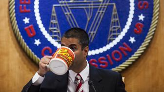 Ajit Pai, chairman of the Federal Communications Commission (FCC), drinks from an oversized coffee mug during an open meeting in Washington, D.C., U.S., on Thursday, Nov. 16, 2017. The FCC plans to vote in December to kill the net neutrality rules passed during the Obama era. Photographer: Zach Gibson/Bloomberg via Getty Images