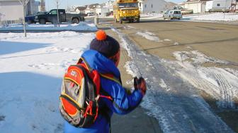 A young boy jumps excitedly as the bus pulls up (slight motion blur on boy)