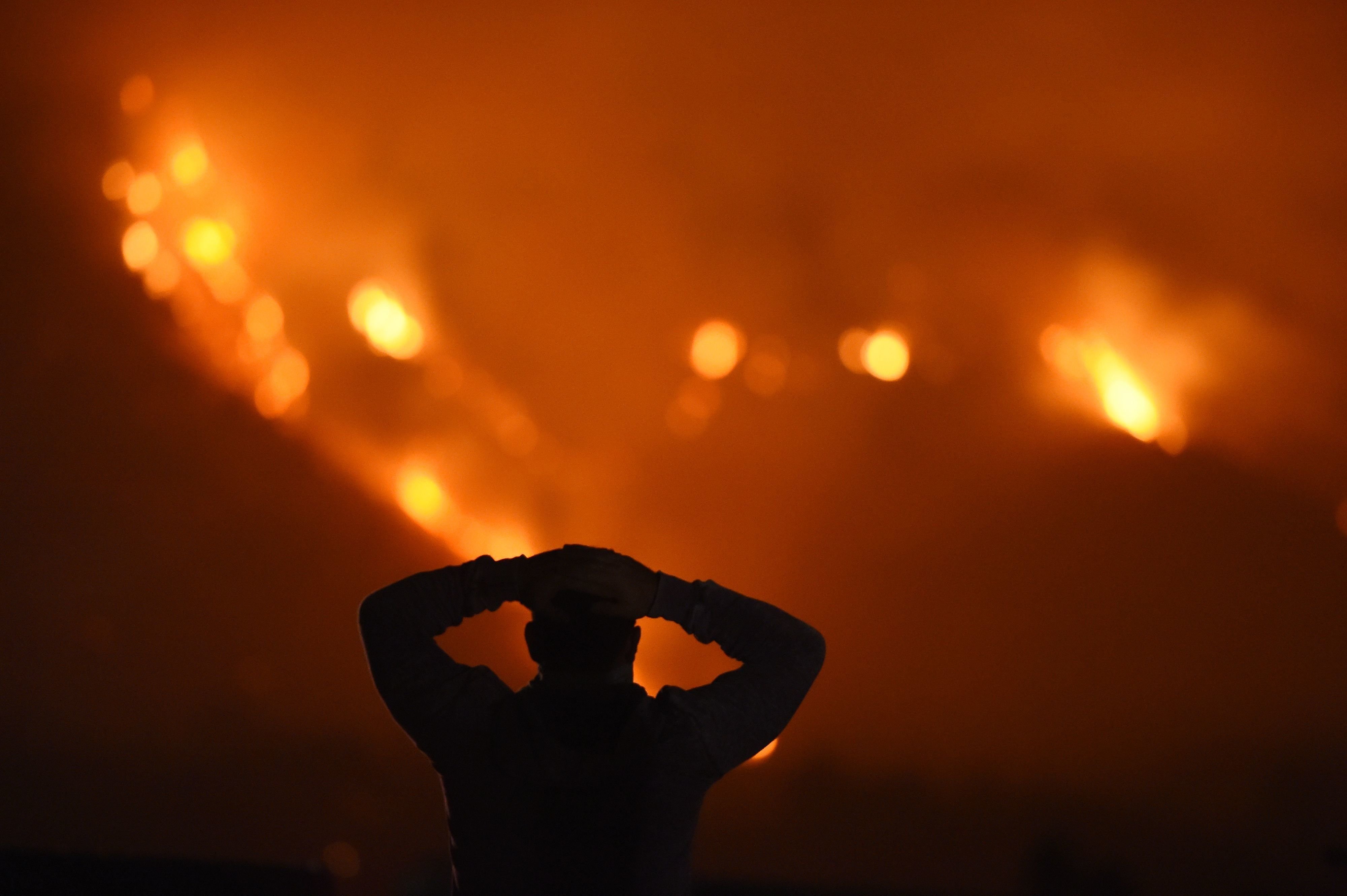TOPSHOT - A man watches the Thomas Fire in the hills above Carpinteria, California, December 11, 2017. The Thomas Fire in California's Ventura and Santa Barbara counties has consumed more than 230,000 acres over the past week making it the fifth largest fire in the state's history. / AFP PHOTO / Robyn Beck        (Photo credit should read ROBYN BECK/AFP/Getty Images)