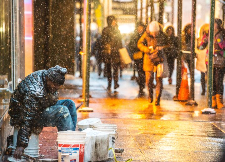 A homeless man sits outside during a snowfall in New York City on Jan. 25, 2014.