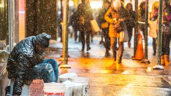 New York, USA - January 25, 2014: Homeless man sitting on New York street under snow. People walking on the street.