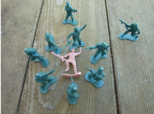 A diorama about a military sexual assault, where the figure in pink is the victim (male, female or transgender) and the green