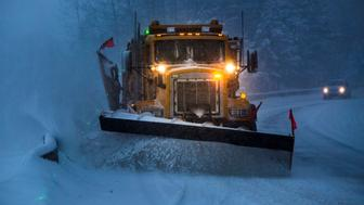 Truck plowing snow off the road at night.