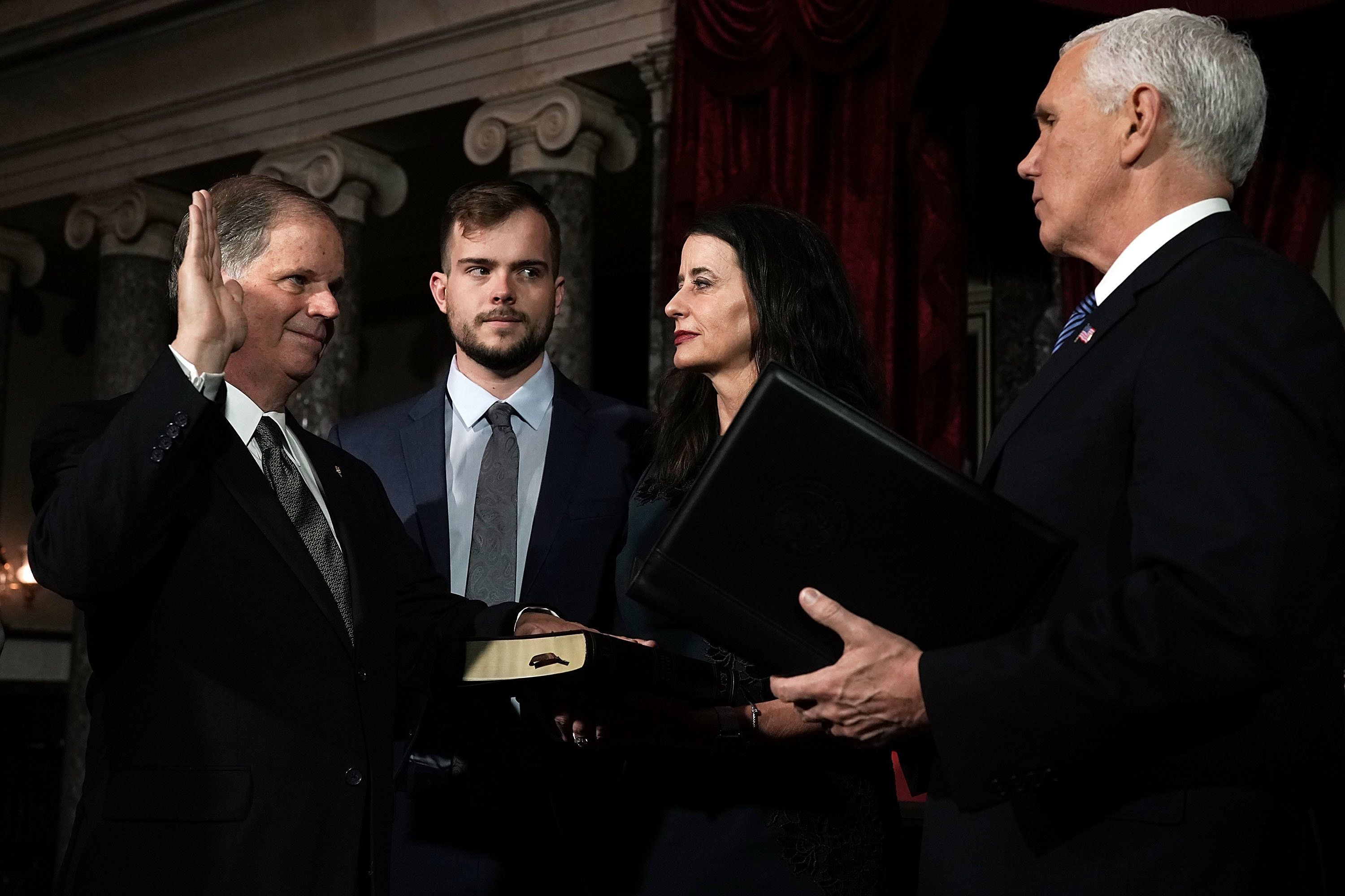 WASHINGTON, DC - JANUARY 03:  U.S. Sen. Doug Jones (D-AL) (L) participates in a mock swearing-in ceremony with Vice President Mike Pence (R) as Jones' wife Louise (3rd L) and son Carson (2nd L) look on at the Old Senate Chamber of the U.S. Capitol January 3, 2018 in Washington, DC. Jones is the first Democratic senator from Alabama in more than two decades. He defeated Roy Moore leaving Republicans with a 51-49 majority in the U.S. Senate.  (Photo by Alex Wong/Getty Images)