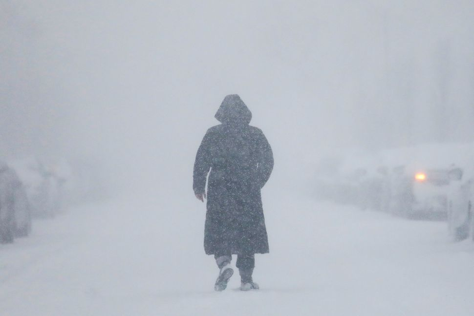 A woman walks down the street during a blizzard in Long Beach, New York.