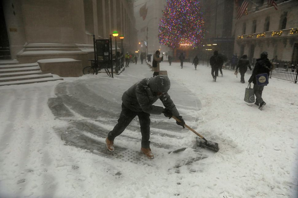 A man shovels snow along Wall Street during a snowstorm in New York City on Jan. 4, 2018.