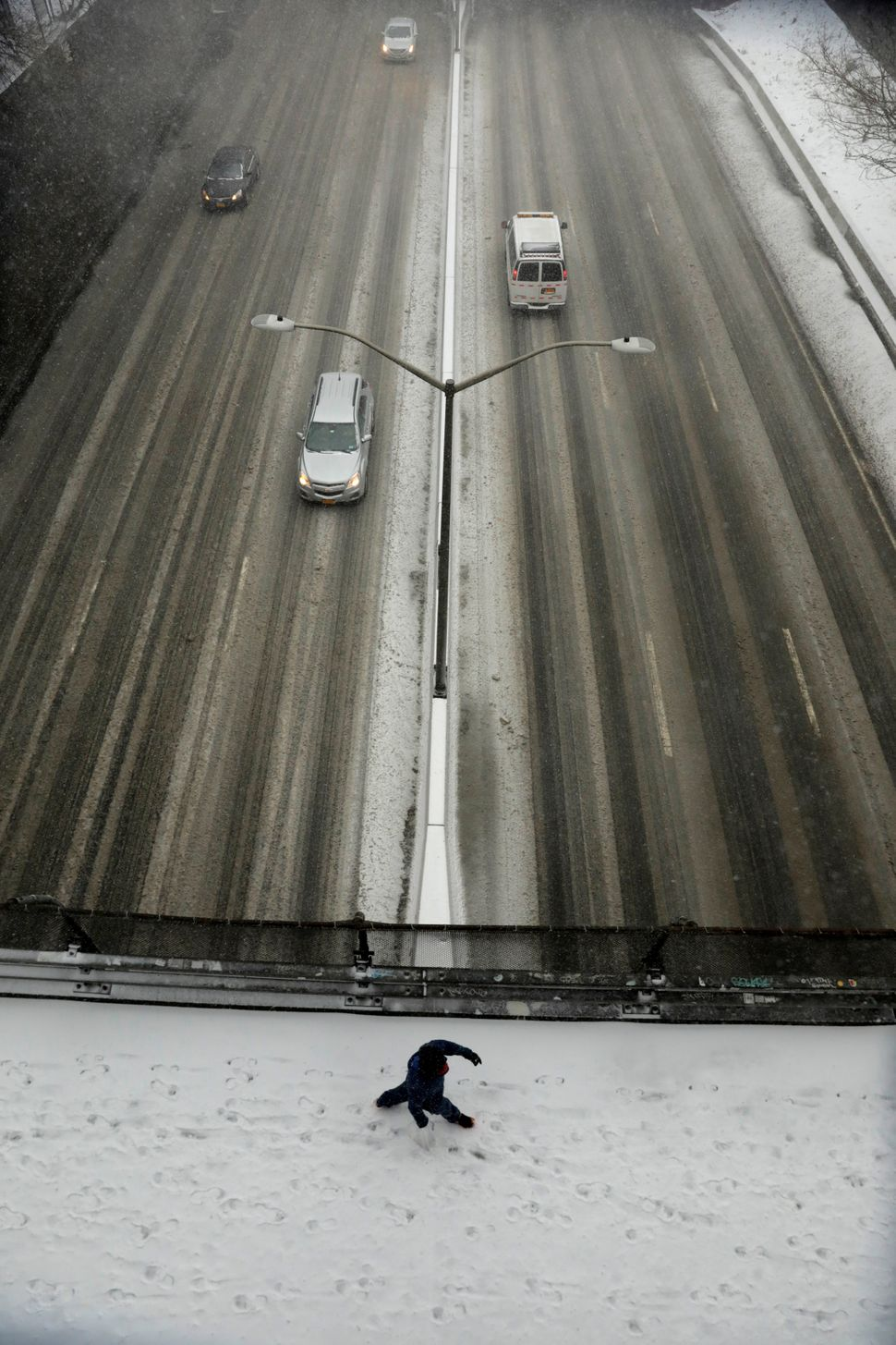 A man walks on a snow-covered bridge, across a highway, during a snowstorm in Brooklyn in New York City on Jan. 4, 2018.