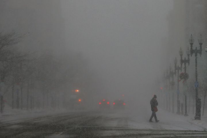 A pedestrian crosses a street during a winter snowstorm in Boston on Thursday.