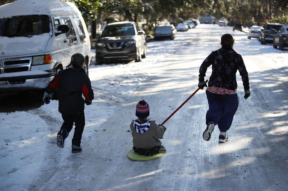 Shebuel Fenster, Jediah Pendergrass and Telem Fenster race down a street covered in snow and ice in Savannah, Georgia.