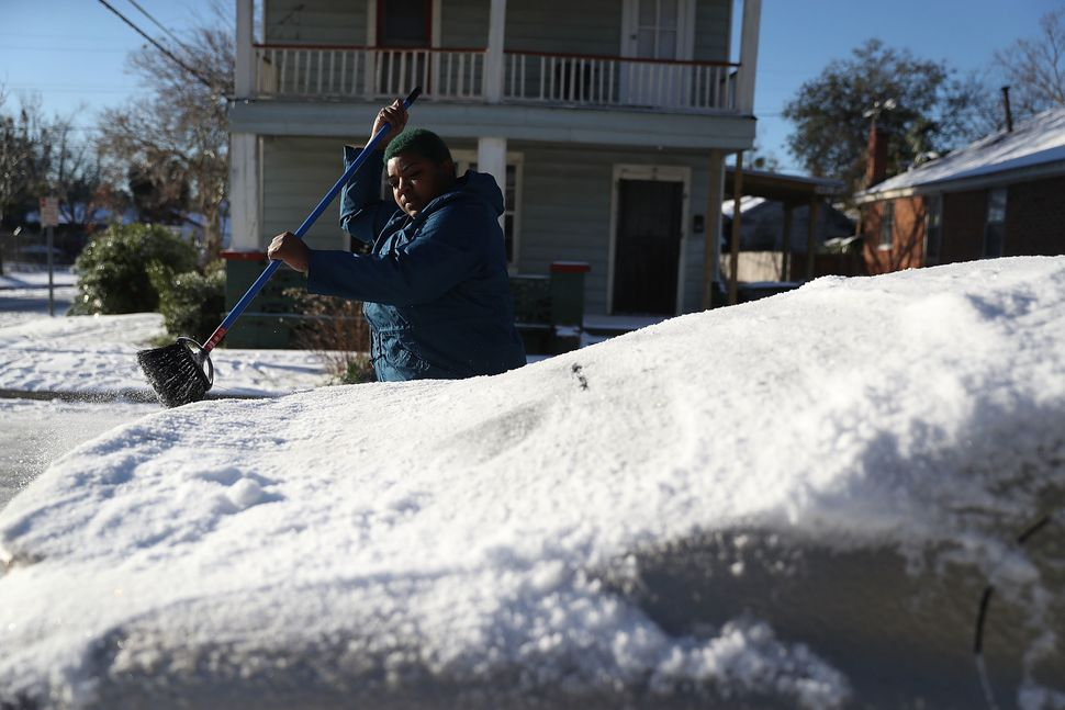 Shannon Fields brushes snow off her car on Jan. 4, 2018 in Savannah, Georgia.
