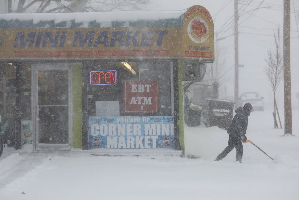 A shopkeeper shovels snow on Jan. 4, 2018 in New Haven, Connecticut.