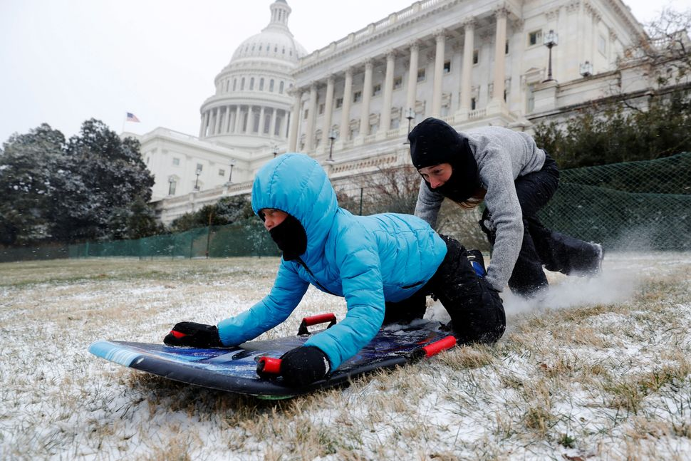 Diego Vazquez gets a push from his mother Genevieve Vazquez in an attempt at sledding in a light snowfall on the west front o