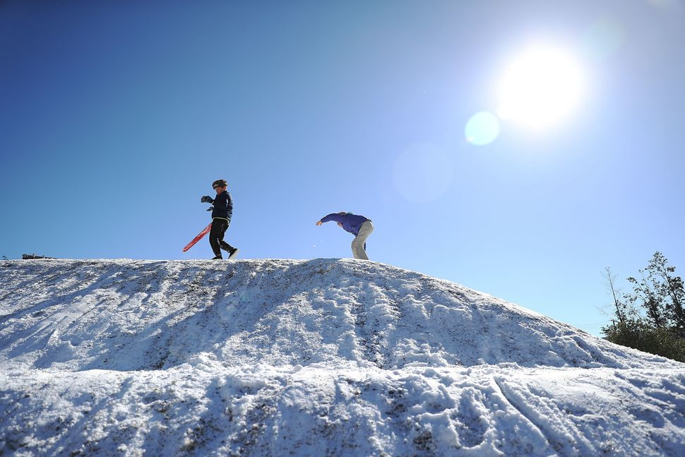 Dylan Zitto and Lily Hock, right, climb a snow-covered hill in Savannah, Georgia.
