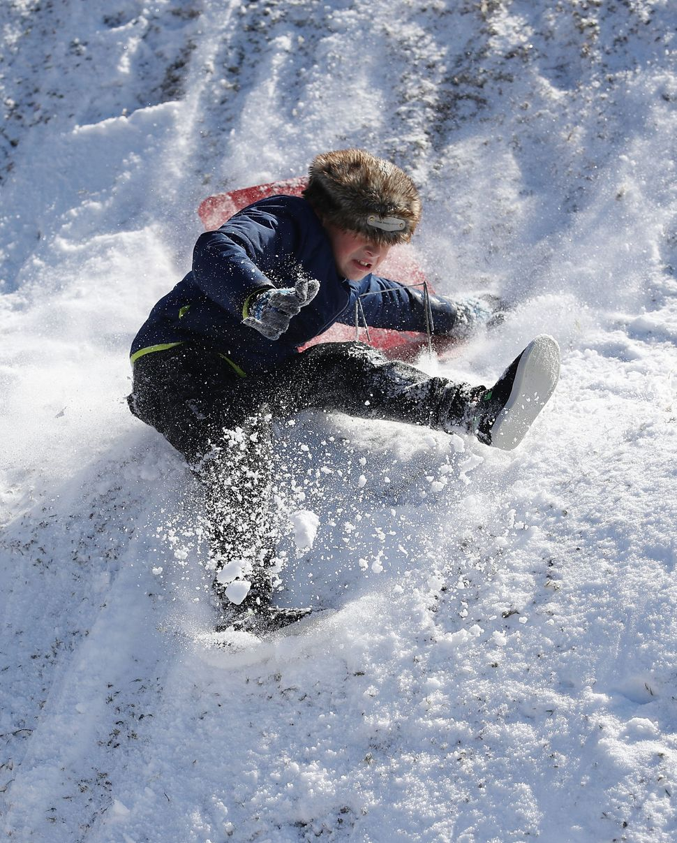 Dylan Zitto slides down a snow-covered hill in Savannah, Georgia, a day after snow fell in the area.