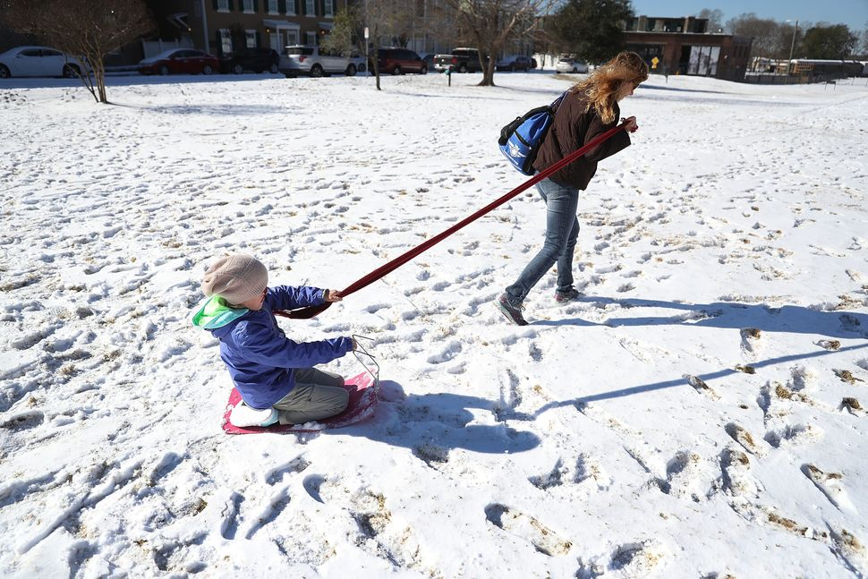 Vickie Hock pulls her daughter Lily Hock through a snow-covered field in Savannah, Georgia.