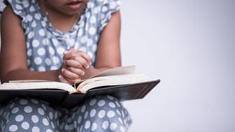 Little girl hands folded in prayer on a Holy Bible on white background  for faith concept in vintage color tone