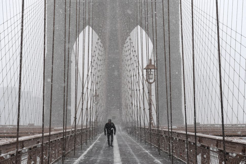A pedestrian walks through blinding snow across the Brooklyn Bridge during Storm Grayson in New York City on January 4, 2018.