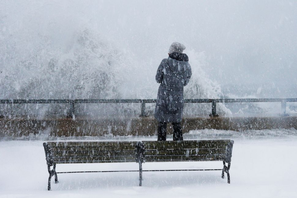 A woman watches as ocean waves overtop the seawall during a winter snow storm in the Boston suburb of Lynn, Massachusetts on