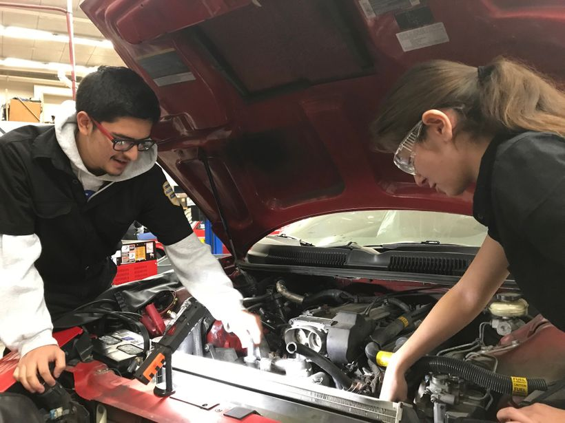 Students at an Eden Area ROP's auto shop class work on a car engine.