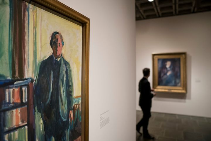 "A man pauses in the self-portrait section of the Edward Munch exhibition titled ""Between The Clock and The Bed"" at the Met Br"