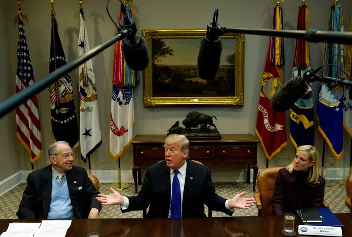 Sen. Chuck Grassley (R-Iowa) and Homeland Security Secretary Kirstjen Nielsen sit next to President Donald Trump at a me