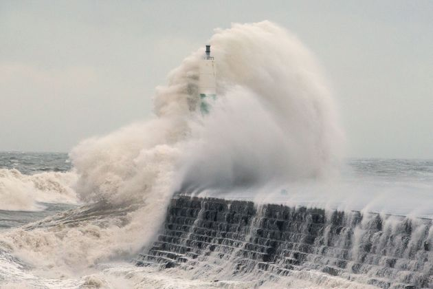 Waves crashing over the stone jetty wall in Aberystwyth on 3