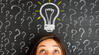 Question marks and one glowing light bulb above head of young woman. Insight, inspiration, eureka, aha moment, making decision, thinking concept on blackboard