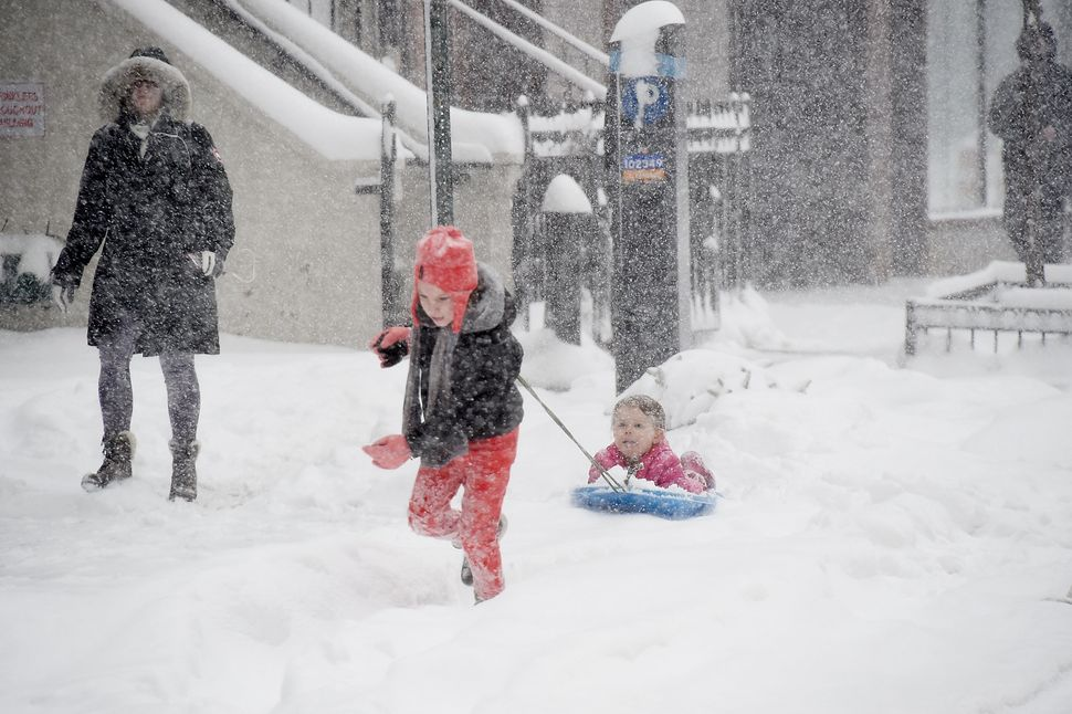 Children sled on the sidewalk during a massive winter storm in New York City.