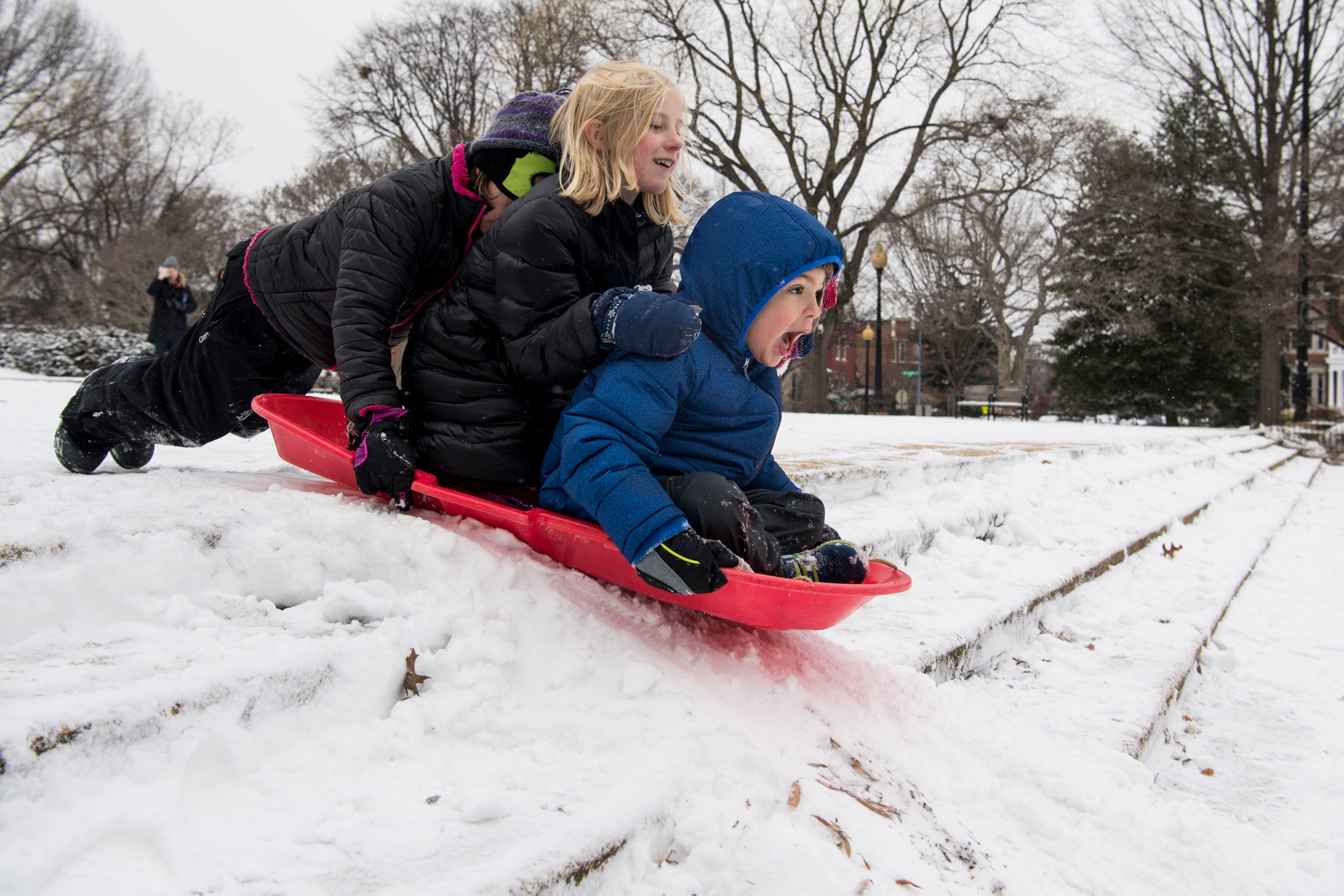 Robbie Schmieder, 5, right, Camilla Minelli, 7, center, and Iris Drager, 9, ride a sled down a small set of stairs in Lincoln