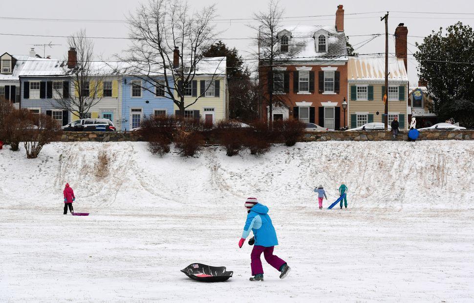 Children play in the snow at Windmill Hill Parkin Alexandria, Virginia.