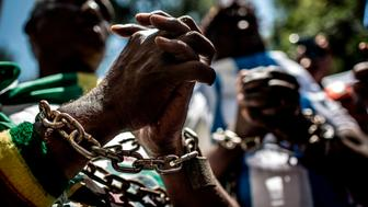 Members of the Africa Diaspora Forum (ADF), civil society organisations, churches, trade unions and other coalitions wear chains and shout slogans during a demonstration against the slave trade and human trafficking in Libya on December 12, 2017 at the Union Buildings in Pretoria. The UN Security Council on December 7 said reports that migrants detained in Libyan camps were being sold into slavery could amount to 'crimes against humanity' in a joint statement of condemnation. / AFP PHOTO / GULSHAN KHAN        (Photo credit should read GULSHAN KHAN/AFP/Getty Images)