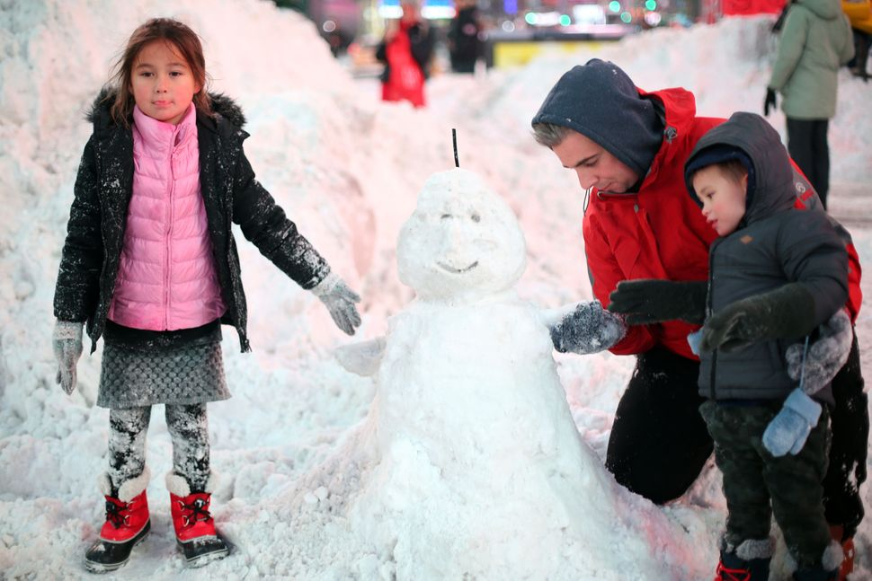 Children make a snowman in Times Square in New York.