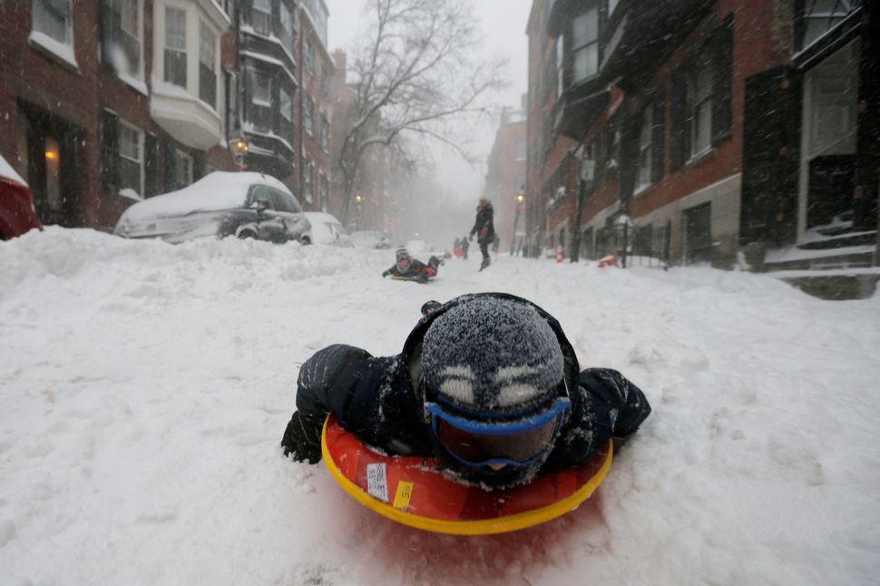 A boy sleds down a Beacon Hill street in Boston.