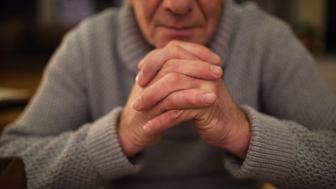 Unrecognizable senior man in gray sweater at home in his living room praying, hands clasped together, eyes closed