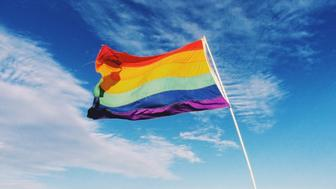 Gay rainbow streaming flag and the blue sky