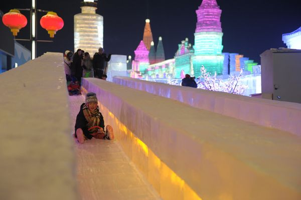 People visit the illuminated ice castle.