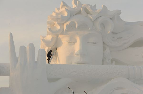 A worker carves a snow sculpture at the Harbin International Snow Sculpture Art Expo.