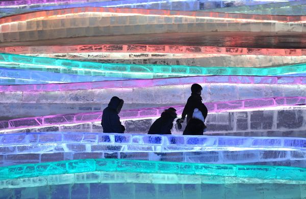 Tourists walk among the various ice sculptures.