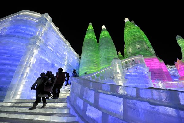 Tourists visit illuminated ice sculptures at the Ice and Snow World park.