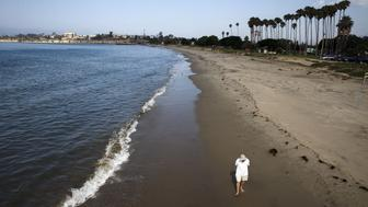 A man walks along the Pacific Ocean at Goleta Beach Park in Goleta, California July 30, 2015. The U.S. Coast Guard was investigating a large, patchy oil sheen that appeared off the Southern California coast west of Santa Barbara on Wednesday, not far from the site of a petroleum pipeline spill in May, officials said. The slick, spanning approximately 3 square miles (8 square km) of the Pacific about 1,000 yards (meters) from shore, was spotted off Goleta State Beach, but the origin of the sheen was unknown, said Coast Guard spokeswoman Petty Officer Sondra-Kay Kneen. REUTERS/Patrick T. Fallon