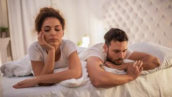 Young couple lying in bed while having problems in their relationship.