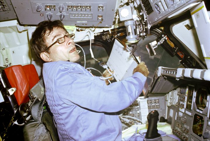 John Young prepares to log flight-pertinent data in a notebook aboard the Space Shuttle Columbia in April 1981.