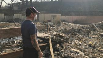 Richie Fredell, 38, a paramedic, looks at the remains of his childhood home in Ventura, California, U.S. December 8, 2017. Picture taken December 8, 2017. REUTERS/Ben Gruber