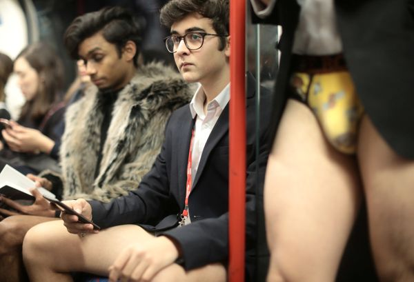 Passengers without trousers travel on a London Underground train.